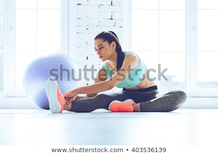 beautiful fitness woman doing stretching exercises stock photo © deandrobot