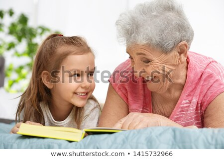 Grandmother reading a book to her granddaughter. Stock photo © choreograph