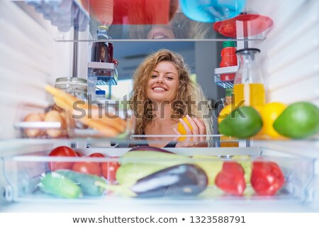 Pretty, young woman taking groceries out of the fridge Stock photo © lightpoet