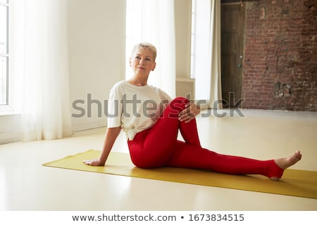 woman doing twist in lotus pose at home Stock photo © dolgachov