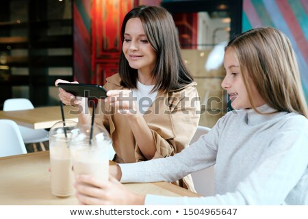 Pretty young brunette woman with smartphone taking photo of two milk cocktails Stock photo © pressmaster