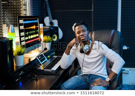 Young successful African man in casualwear sitting by workplace in studio Stock photo © pressmaster
