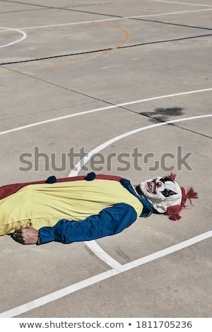 scary clown on an outdoor basketball court Stock photo © nito