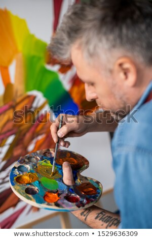 Contemporary professional painter mixing gouache or oil color on palette Stock photo © pressmaster