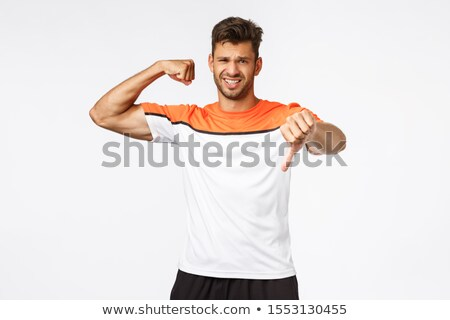 Handsome fit and muscular man dont like his body shape, show thumb down as raise one hand with bicep Stock photo © benzoix