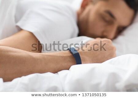 close up of man sleeping with activity tracker Stock photo © dolgachov