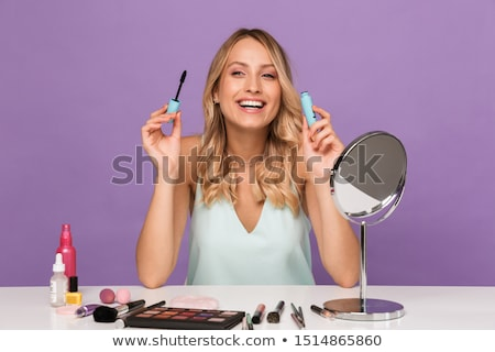 Woman posing isolated holding lash mascara. Stock photo © deandrobot