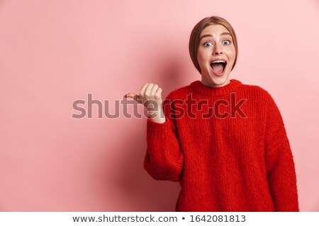 Photo of shocked woman expressing surprise and pointing finger aside Stock photo © deandrobot