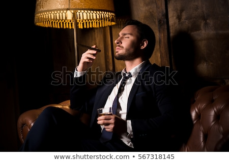 fashion man smoking a cigarette while relaxing stock photo © feedough