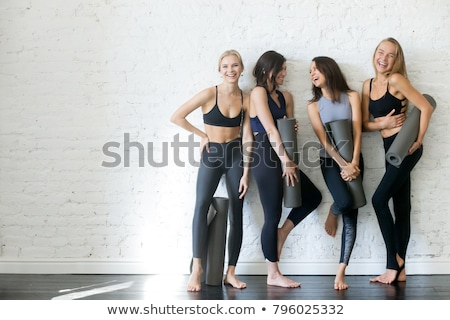 smiling young woman standing with yoga mat stock photo © deandrobot
