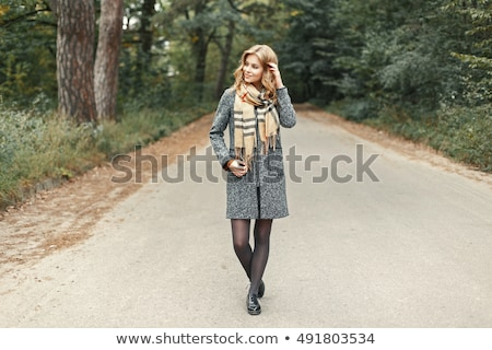 Pretty woman in green coat and scarf Stock photo © deandrobot