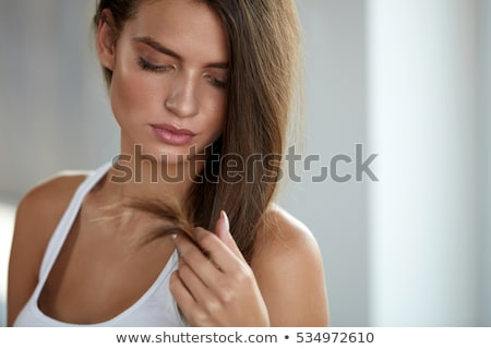Upset beautiful woman looking on splitting ends of long hair  Stock photo © deandrobot