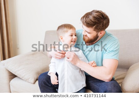 Happy father sitting on sofa and dressing his little son Stock photo © deandrobot
