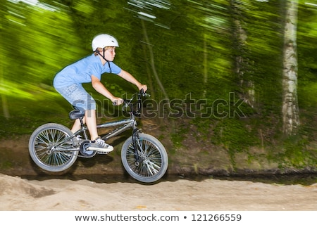 child has fun jumping with the bike over a ramp  Stock photo © meinzahn