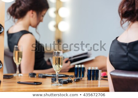 pensive woman sitting near mirror with bulbs in dressing room stock photo © deandrobot