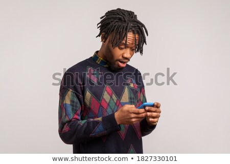surprised casual man looking at mobile phone with big eyes stock photo © deandrobot
