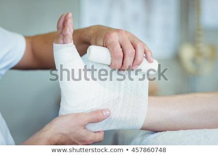Physiotherapist putting bandage on injured feet of patient Stock photo © wavebreak_media