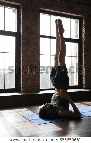 Concentrated strong sportsman in gym make yoga sport exercises Stock photo © deandrobot
