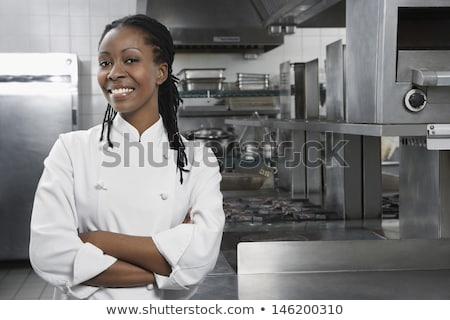 smiling female chef with hands crossed in the kitchen stock photo © wavebreak_media