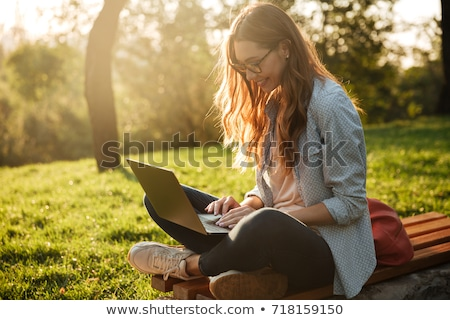 smiling young brunette woman sitting in park with laptop computer stock photo © deandrobot