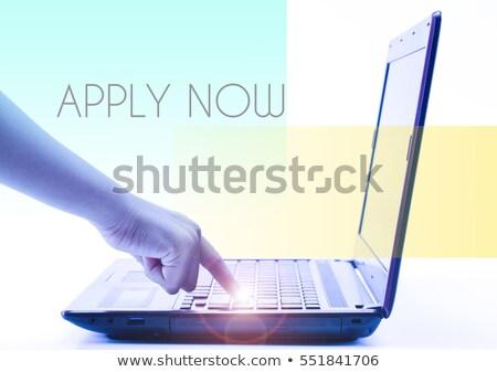 apply now on laptop in modern workplace background stock photo © tashatuvango