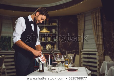 waiter opening wine bottle at a table stock photo © is2