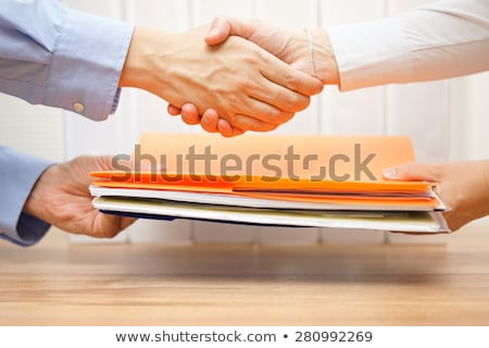 Businesswoman passing folder to client Stock photo © IS2