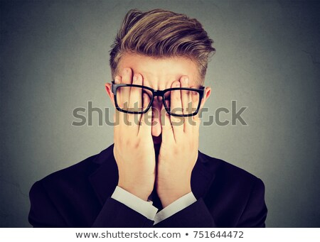 young man in glasses covering face eyes with both hands Stock photo © ichiosea