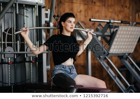Strong disabled sports woman make sport exercises with barbell equipment in gym. Stock photo © deandrobot