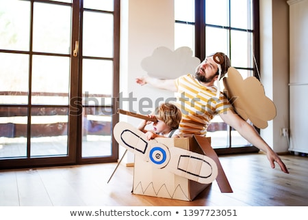 happy little girl in pilot hat playing at home Stock photo © dolgachov