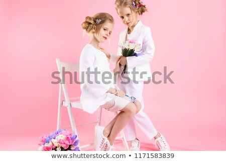Twins girls in light clothes with bouquets of flowers posing near a chair on a pink background. Stock photo © Traimak