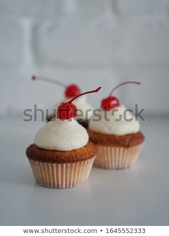 Vanilla cupcake with whipped cream and cherry stock photo © TasiPas