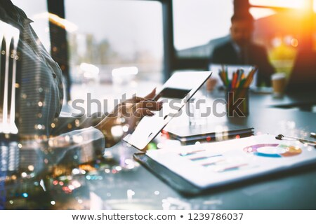 Businesswoman works in office with a tablet. Concept of internet sharing and company startup. double Stock photo © alphaspirit