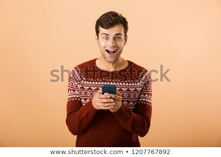 Image of happy man 20s with stubble wearing knitted sweater usin Stock photo © deandrobot