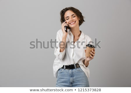 young woman posing isolated over grey wall background using mobile phone drinking coffee stock photo © deandrobot
