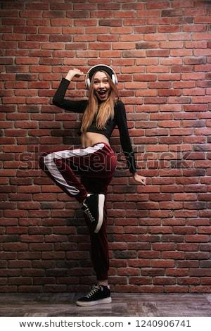 Full length image of sporty hip hop woman 20s wearing headphones Stock photo © deandrobot