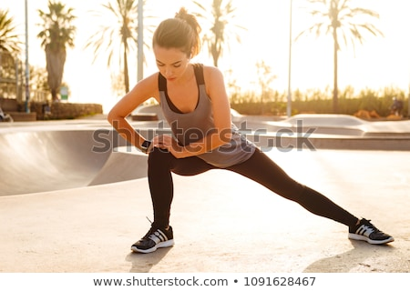 Sports woman in park outdoors make sport stretching exercises. Stock photo © deandrobot