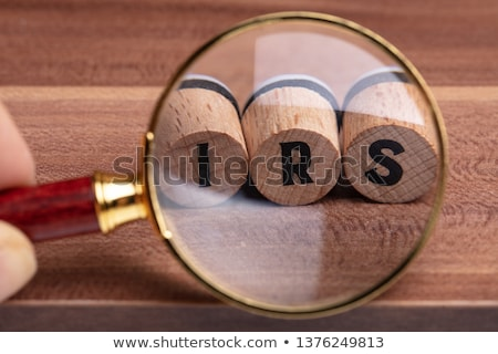 hand holding magnifying glass over wooden cork with irs text stock photo © andreypopov