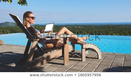 Young restful female lying by poolside while sunbathing Stock photo © pressmaster