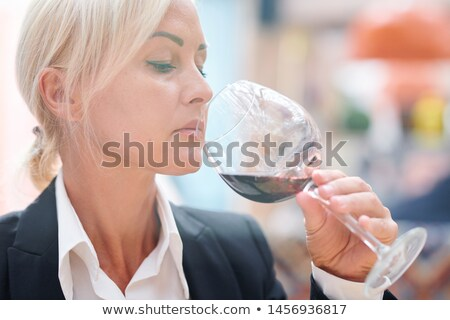 Professional female sommelier smelling red wine while checking its quality Stock photo © pressmaster