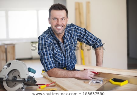 Carpenter working at saw looking into camera Stock photo © Kzenon