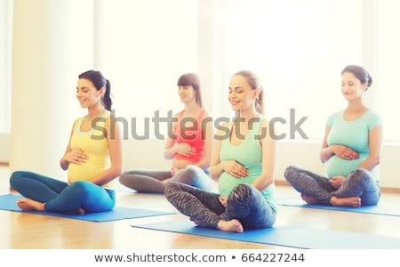happy pregnant women meditating at gym yoga Stock photo © dolgachov