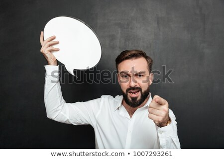 Joyful man pointing at blank speech ballon. Stock photo © lichtmeister