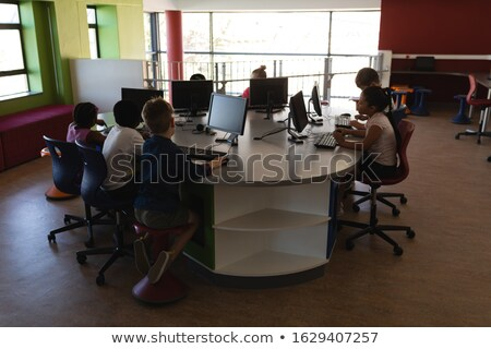 Rear view of  a group of schoolkids studying on desktop pc in school Stock photo © wavebreak_media