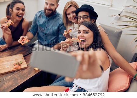 happy friends photographing at rooftop party stock photo © dolgachov