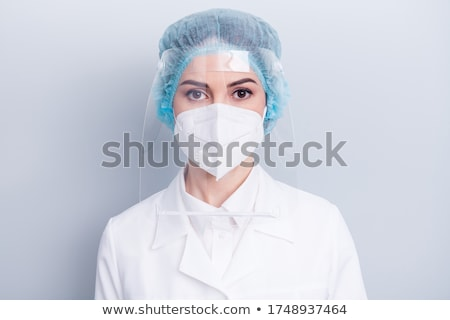A surgeons , woman wearing protective uniforms,caps and masks an Stock photo © Lopolo