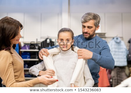 Young parents helping their daughter with trying on new warm waistcoat Stock photo © pressmaster