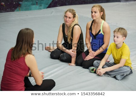 two women and schoolboy sitting on mat in front of their sports instructor stock photo © pressmaster