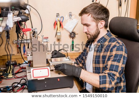 bearded repairman in gloves sitting in front of equipment for gadget repair stock photo © pressmaster