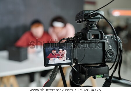 Two young contemporary male vloggers on screen of video camera in studio Stock photo © pressmaster